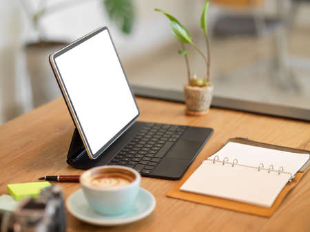 Closeup image of Portable digital tablet with keyboard stand on table at cafe workspace. coffee cup, blank diary on table