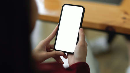 Close-up of a woman using a modern smartphone to research business trends and read the most latest online business columns. screen mockup Фото со стока