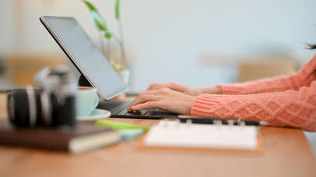 Side view, closeup of a work table with female hands typing on tablet keyboard computer, working from home, remote working.