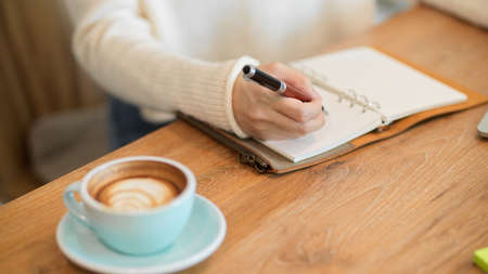 Cropped closeup image of Female in white sweater writing or taking notes something on her notebook, tasty coffee on the table.