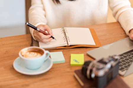 Cropped image of young woman writing her daily routines on her personal diary book at cafe