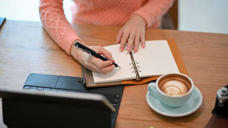 Cropped image of young female freelance writer writing her stories on her personal diary book, tablet on table.