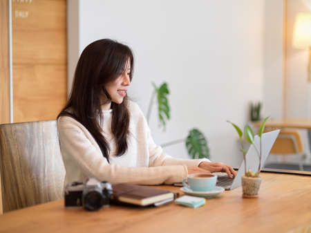Young Asian beautiful girl working with laptop computer in a coffee shop, freelancer, businesswoman, studying online, browsing the internet. Фото со стока