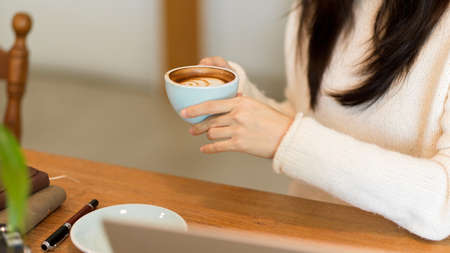 Cropped image of Relaxed female in comfy white sweater drink, sip, hold hot cappuccino coffee cup to warm herself.