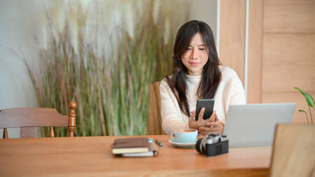 Beautiful young female sits in a coffee shop and using smartphone, laptop computer, camera and stuff on the table.
