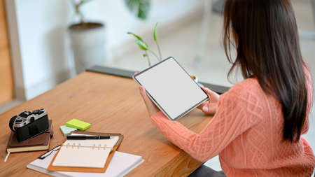 Millennial female in pink sweater holding, using, working, looking on portable digital tablet computer at workplace