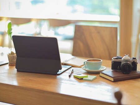 Modern cozy and minimalist workspace with digital tablet, vintage camera, coffee cup and stationery on wooden table