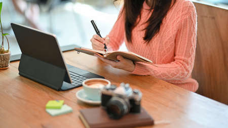 Cropped image of female writer planning her working process on notebook while working on tablet computer at cafe.