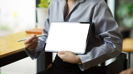Cropped image of businesswoman shows and explains the information on tablet screen to her coworker. tablet blank screen mockup.