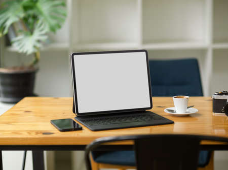 Modern portable tablet computer with magic keyboard in blank screen mockup stand on wooden table in coffee shop Фото со стока