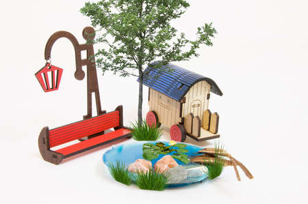 Wooden red park bench maquette and Light bulb, small lake, caravan, plantain Stock Photo