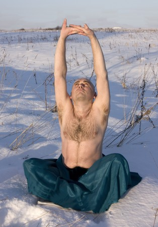 man practicing yoga  over white snow in winter