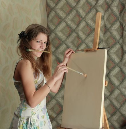 a woman smiling while painting a picture on her blank white canvas Stock Photo - 4962387