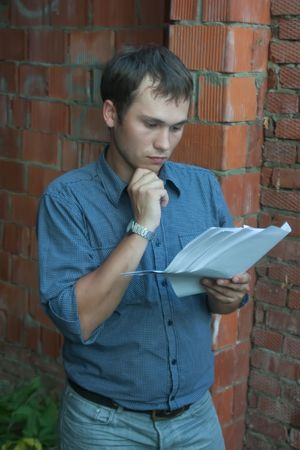 tasker: a foreman with documents against  the brick wall Stock Photo