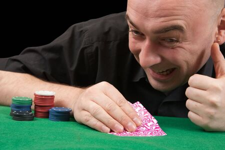 Poker gambler in black shirt close-up. Focus on the hand and eye