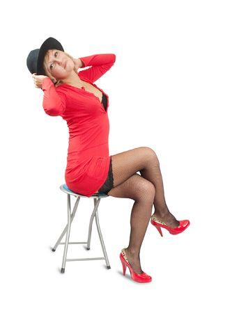 Fashion type photo of an stunningly beautiful young woman posing on stool