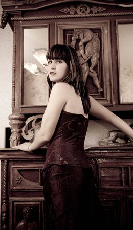 The posing girl at vintage room in style old-fashioned  photo