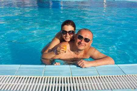 couple in the swimming pool having a cocktail photo