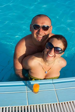 happy couple in the swimming pool in a hotel photo