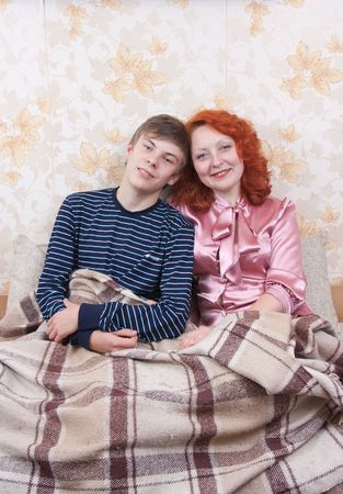 son with mother sitting on sofa and smiling Stock Photo - 6677924