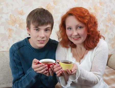 smiling woman and teen boy have tea on sofa at home photo