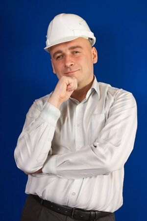 tasker: caucasian foreman in white hard hat smiling over blue Stock Photo