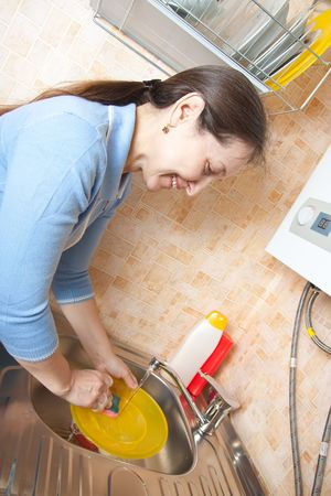 Woman washing dirty dishes in the kitchen sink photo