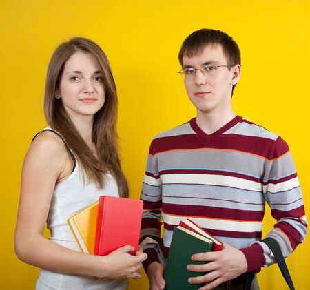 Two young students with books. Over yellow background Stock Photo - 6808645