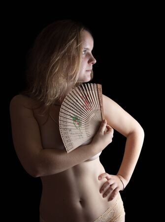 Portrait of blonde naked girl with fan over black Stock Photo - 6808671