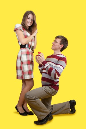 propose: Young man romantically proposing to surprised girlfriend and offering engagement ring
