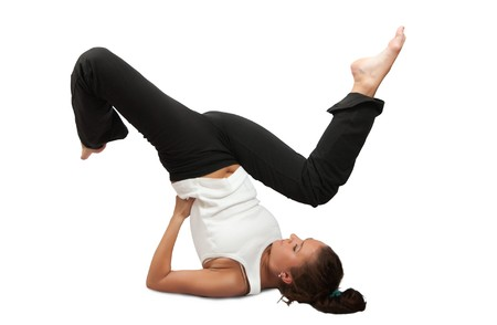 fit brunette in black sportswear practicing yoga over white