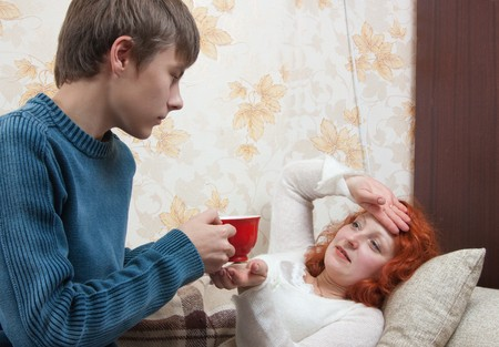 Mother is sicking and her son giving a cup of tea photo