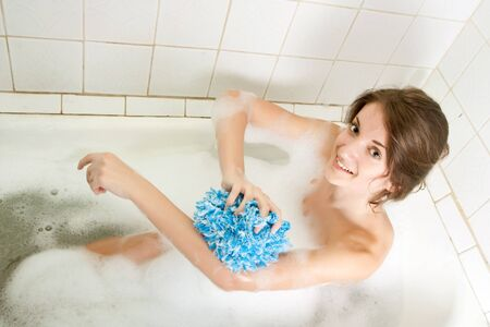 The brunette girl washes in a bath