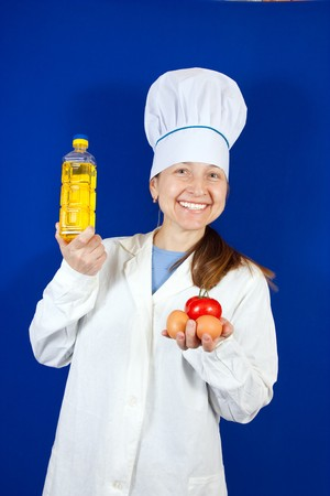 female cook holding  dietetic foods over blue background photo