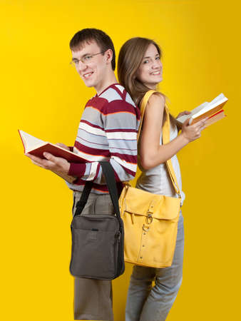 Two young students with books. Over yellow background photo