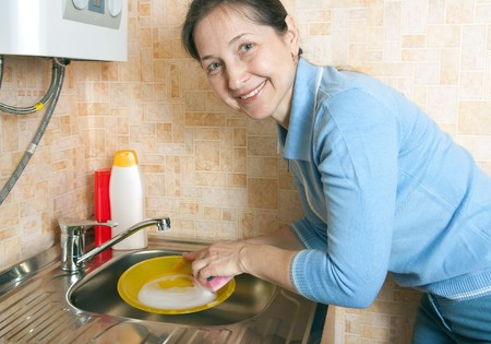 beautiful woman is washing the dishes in the kitchen photo