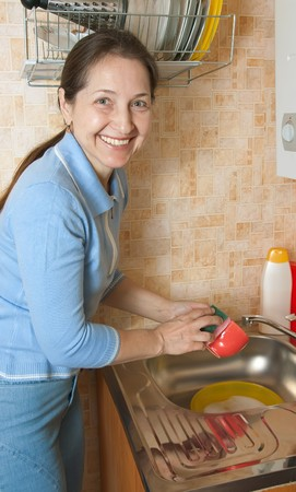 Woman washing dirty dishes in the kitchen sink Stock Photo - 7042517