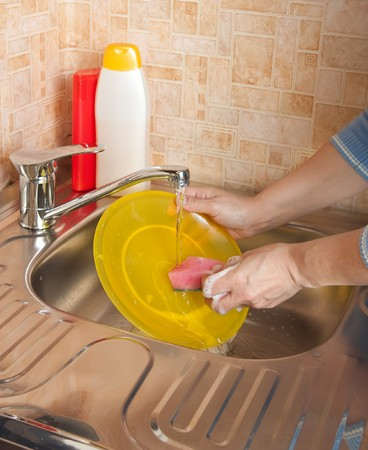 woman is washing the dishes in the kitchen photo