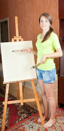 woman smiling while painting a picture on her blank white canvas Stock Photo - 7042487