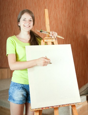 Young painter near easel in living room Stock Photo - 7042489