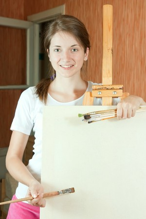 Pretty girl with brushes standing  near easel indoor Stock Photo - 7042482
