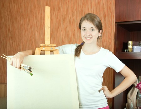 Pretty girl with brushes standing  near easel indoor Stock Photo - 7042471