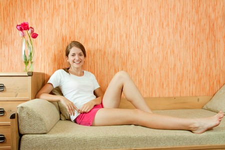 teen legs: Pretty teen girl in shorts sitting on sofa at home Stock Photo