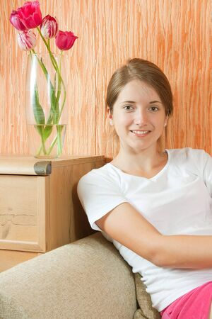 Pretty teen girl in shorts sitting on sofa at home photo