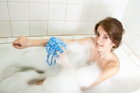 young beautiful girl in a bath with shower puff  Stock Photo - 7073285