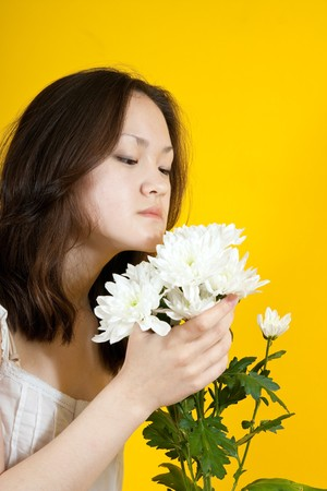 Photo of an attractive asian girl with flowers over yellow Stock Photo - 7111005