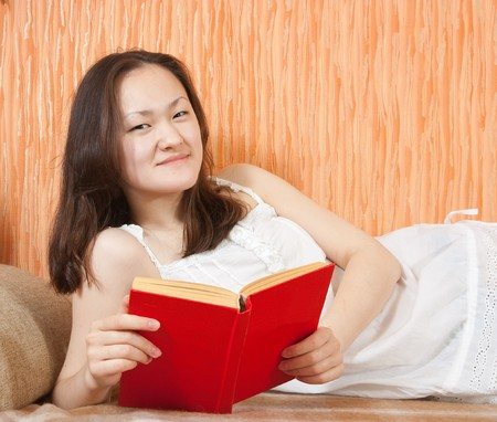 Photo of an reading attractive asian girl  on sofa photo