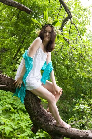 beauty Asian girl with Lily of the valley chaplet in the forest photo