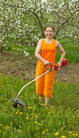 Happy  elderly  Woman Gardener with grass-cutter photo