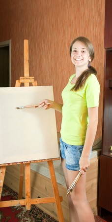 Pretty girl with brushes standing  near easel indoor Stock Photo - 7291468
